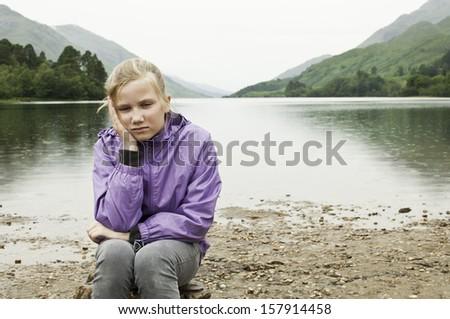 Child left alone in the rain - stock photo