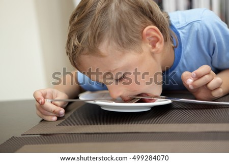 Child licking remnants of food from plate in cafe