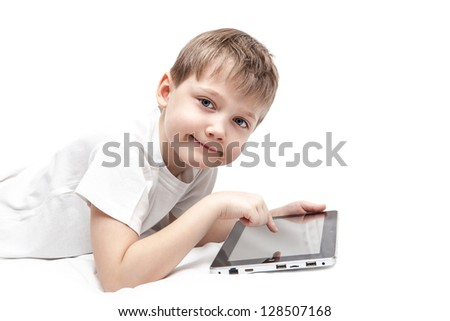 Child lies on a bed with a tablet pc - stock photo