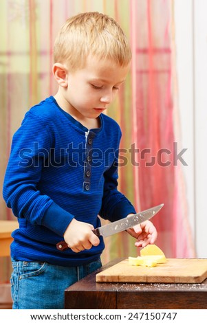 Child little boy playing dangerous game with a kitchen knife cut apple, making salad at home.