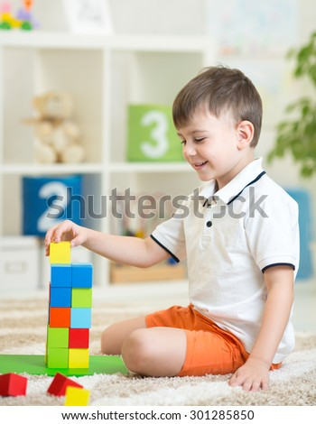 child little boy playing with wooden cubes toys in nursery at home or daycare center - stock photo