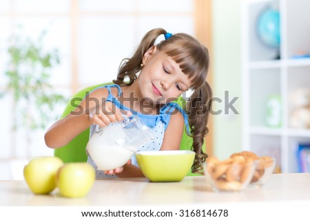 Child little girl having breakfast at nursery - stock photo