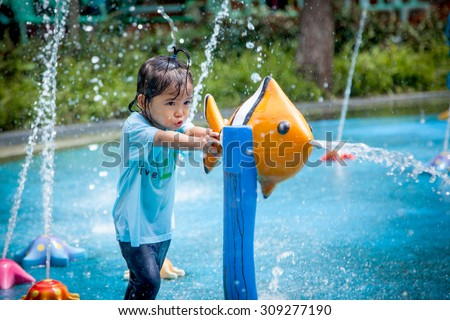 Child little girl having fun to play with water in park fountain in summer time - stock photo