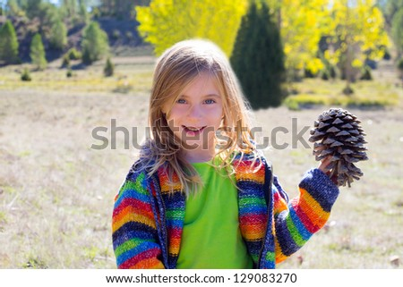 Child little girl holding pine cone in winter fall at nature outdoor - stock photo