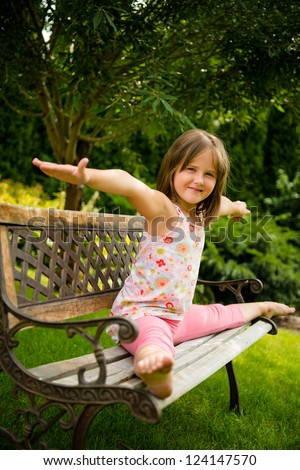 Child (little girl) performing gymnastic pose on bench outdoor in backyard