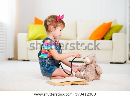 Child little girl playing doctor in the children's room - stock photo