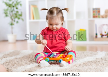 Child little girl plays a musical instrument xylophone - stock photo