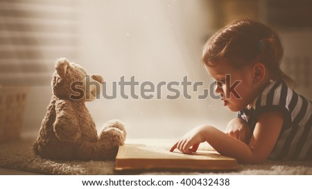 child little girl reading a magic book in the dark home with a toy teddy bear - stock photo