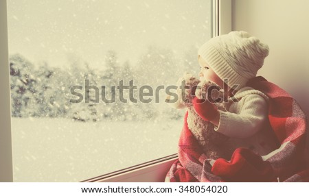 child little girl sitting by the window with a teddy bear and looking at the winter forest - stock photo