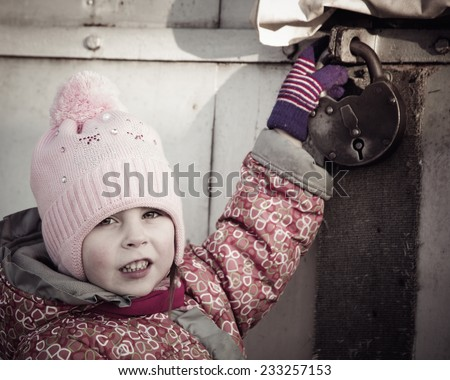 child locked behind a metallic gate