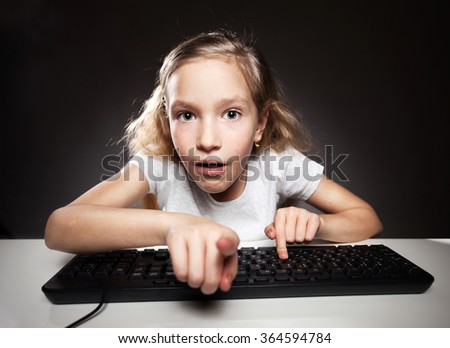 Child looking at a computer. Computer addiction - stock photo