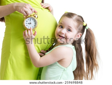 child looking at alarm clock and pregnant woman belly - stock photo