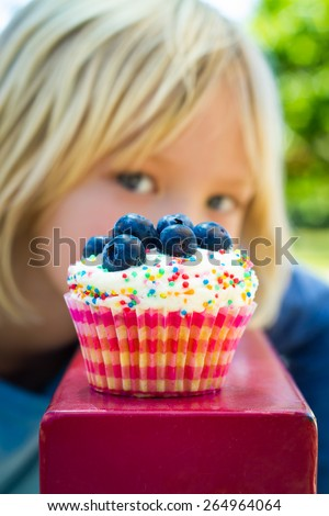 Child looking at colorful tempting cupcake treat. Cupcake is in focus. - stock photo