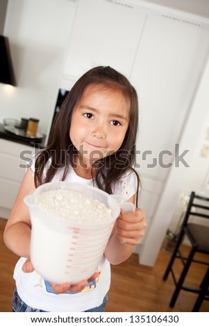 Child looking at the camera holding a measuring cup filled with flour - stock photo