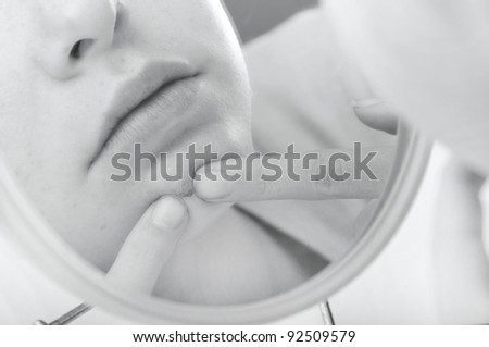 Child looking in mirror picking at pimple - stock photo