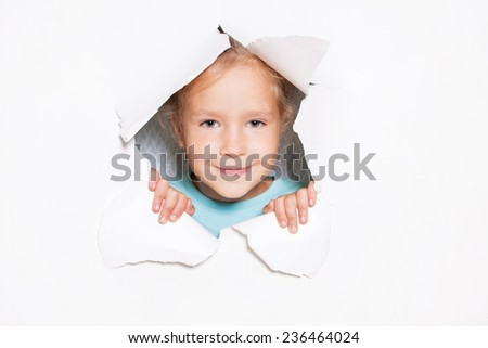 Child looking out of a hole in paper. Banner. Happy girl
