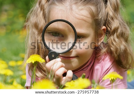 Child looking through a magnifying glass on dandelions. - stock photo