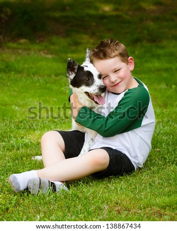 Child lovingly embraces his pet dog, a blue heeler - stock photo