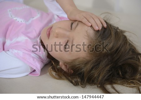 Child lying down suffering from a headache