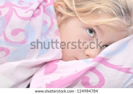Child lying in bed with a pink quilt. - stock photo