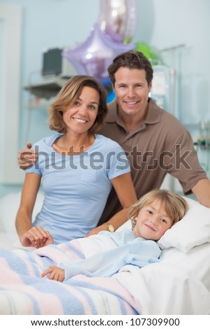 Child lying on a medical bed next to his parents in hospital ward - stock photo