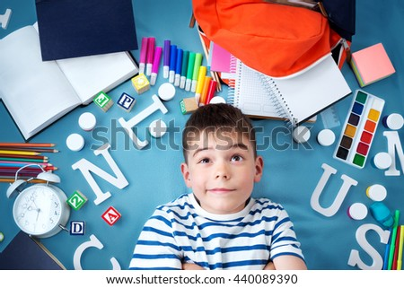 child lying on blue blanket with various school accessories - stock photo