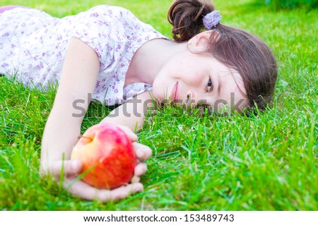 Child lying on grass holding an apple