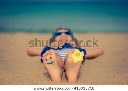 Child lying on sandy beach near blue sea. Summer vacation and healthy lifestyle concept - stock photo