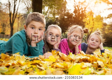 Child lying on the golden leaf - stock photo