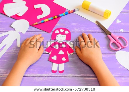Child made an angel doll of cardboard. Childrens hands on a wooden table. Tools and materials for a fun kids art and craft activity. Valentine's day crafts idea for kids