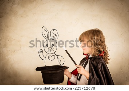 Child magician holding a top hat with drawn rabbit against grunge background. Focus on the hat - stock photo
