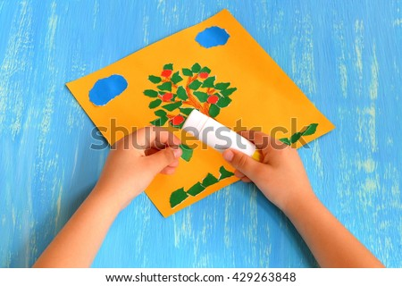 Child makes a torn paper tree. Child holds in his hands a green paper piece and sticks it. Summer tree paper craft. Idea for preschoolers. Home apple tree applique. Step-by-step. Blue wood background. - stock photo