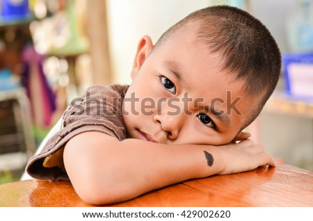 Child making a sad face.Boy has a black birthmark on the arm In Sad mood. Mercury Float with emotion - stock photo
