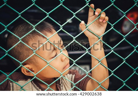 Child making a sad face.boy sad standing alone behind jail.Pensive child looking through.Small boy thinking about something.Depressed Little boy.child in the dark.Image of depressed young boy  - stock photo