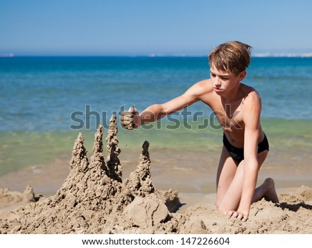 Child making sand castle on beach