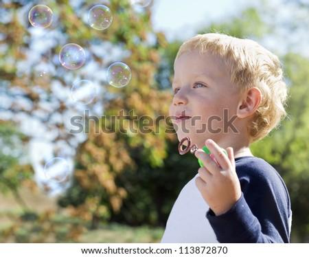 Child making soap bubbles outside - stock photo