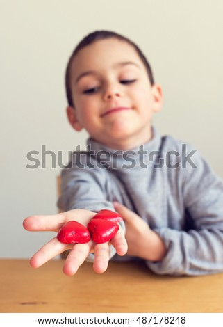 Child offering chocolate heart sweets or candies wrapped in red paper