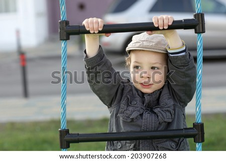 Child on a rope ladder at playground - stock photo