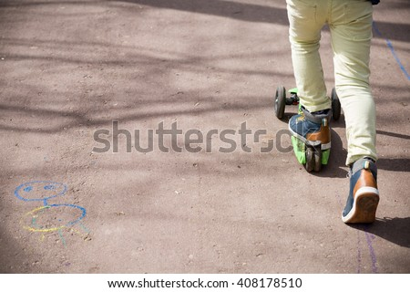 Child on a Scooter. Feet of a kid boy with sneakers on scooter on a sunny day. Pavement with drawings made with chalk. child riding scooter outdoors, active sport kids