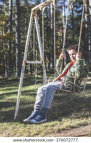 Child on a swing in a forest
