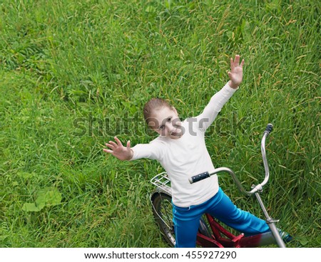 Child on bike driving through the grass.