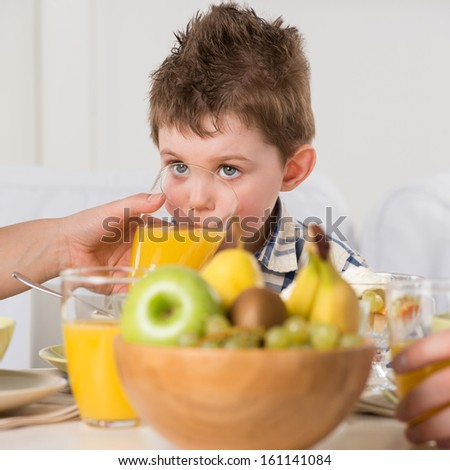 Child on breakfast - drinking juice - stock photo