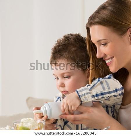 Child on breakfast - making a fruit salad with cream with his mother