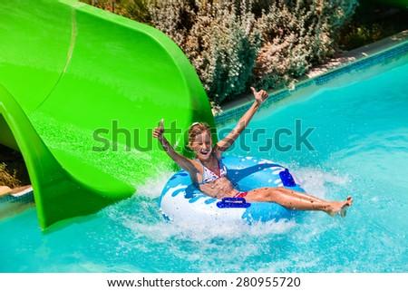 Child on green water slide thumb up at aquapark. Summer holiday. - stock photo