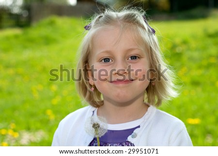 Child on meadow with blowball - stock photo