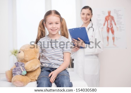 Child on medical exam. Cheerful little girl looking a camera and smiling while doctor standing on the background and holding clipboard - stock photo
