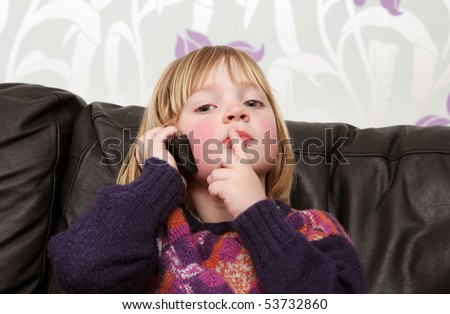 child on mobile phone sat on sofa. boy communicating with wireless telephone - stock photo