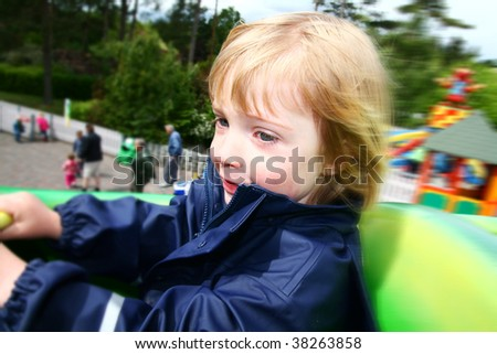 child on ride in them park. toddler on roller coaster at amusement fair