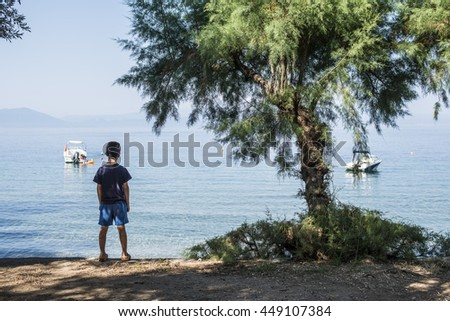 Child on the beach looking at the sea and boats.  - stock photo