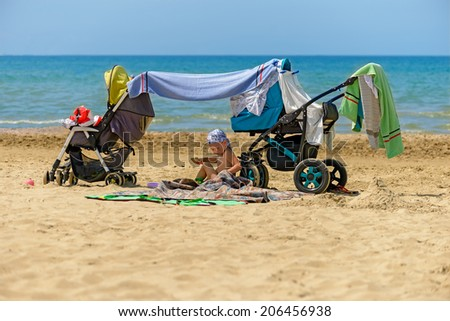 Child on the beach on the sea background - stock photo